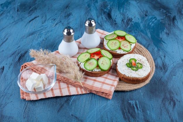 Pyszne tosty ze śmietaną i pokrojonymi ogórkami na niebieskiej powierzchni.