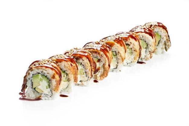 Pyszne uramaki sushi philadelphia z węgorzem, ogórkiem i awokado. klasyczna kuchnia japońska. dostawa jedzenia. na białym tle.