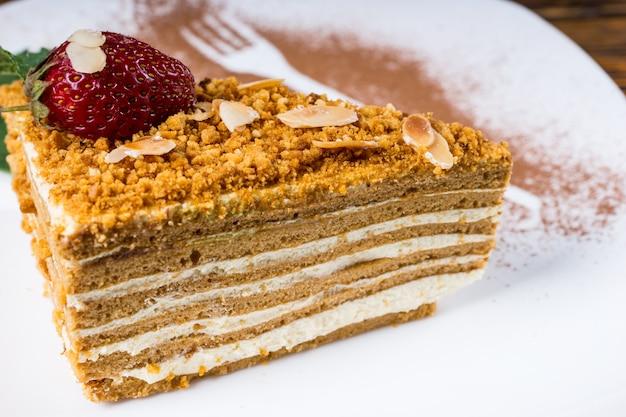 Pyszne warstwowe ciasto migdałowe z kremowym nadzieniem orzechowym zwieńczone świeżą truskawką i miętą podane na talerzu z ozdobnymi sylwetkami widelca i łyżki w proszku czekoladowym, widok z bliska