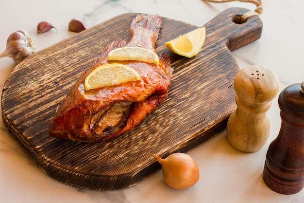 Pyszne wędzone ryby oceaniczne okoń na drewnianej desce do krojenia dla zdrowej żywności, diety lub koncepcji gotowania, selektywne focus.
