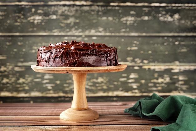 Pyszne wegańskie ciasto czekoladowe na drewnianym stojaku na tępej zielonej rustykalnej ścianie.