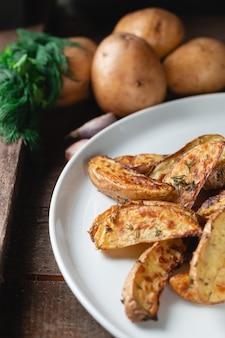 Pyszne wiejskie ziemniaki pieczone w dużym białym talerzu z przyprawami, koperkiem i zieloną cebulą na drewnianym stole