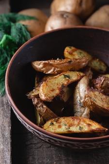 Pyszne wiejskie ziemniaki pieczone w glinianej misce z przyprawami, koperkiem i zieloną cebulą na drewnianym stole