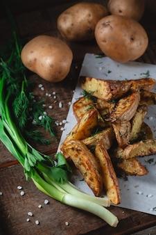 Pyszne wiejskie ziemniaki pieczone z przyprawami, koperkiem i zieloną cebulą na drewnianym stole