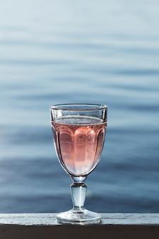 Pyszne wino różane w szklance nad brzegiem morza