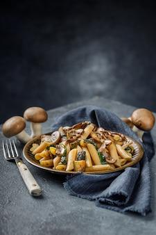 Pyszne włoskie danie, makaron penne z spanach, cukinią i pieczonymi grzybami z czosnkiem na niebieskim marmurowym stole z teksturą z pustym miejscem na tekst. integralny makaron i całe pieczarki