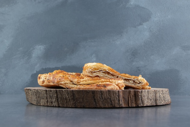 Pyszne wypieki wypełnione mięsem na drewnianym kawałku.