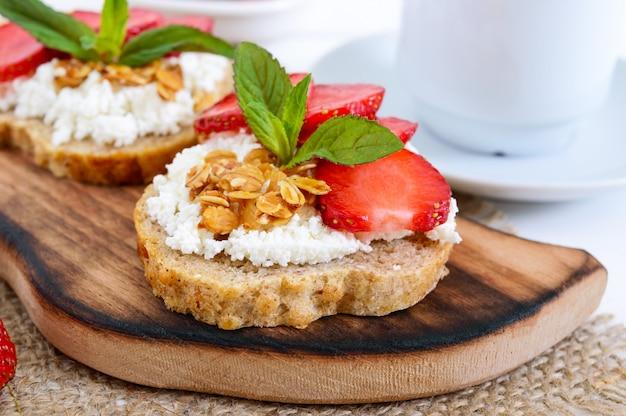 Pyszne zdrowe śniadanie dietetyczne: chleb żytni z twarogiem i truskawkami na białym drewnianym.