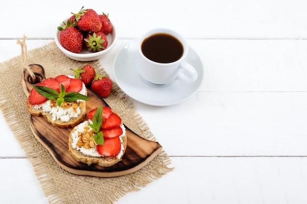 Pyszne zdrowe śniadanie dietetyczne: chleb żytni z twarogiem i truskawkami