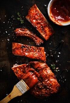 Pyszne żeberka z grilla doprawione ostrym sosem do smażenia i podane na żelaznej patelni