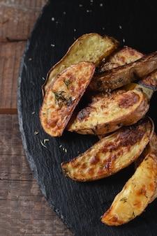 Pyszne ziemniaki pieczone kraj na kamień cięcia łupków na drewnianym stole, widok z góry