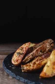 Pyszne ziemniaki pieczone kraju na kamień cięcia łupków na drewnianym stole