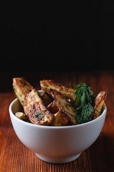 Pyszne ziemniaki pieczone wiejskie w glinianej misce z przyprawami, koperkiem i zieloną cebulą na drewnianym stole, miejsce na tekst