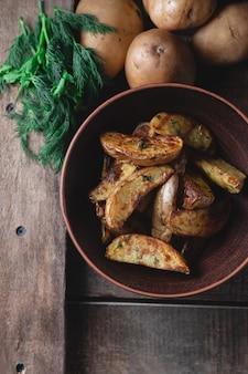 Pyszne ziemniaki pieczone wiejskie w glinianej misce z przyprawami, koperkiem i zieloną cebulą na drewnianym stole, widok z góry