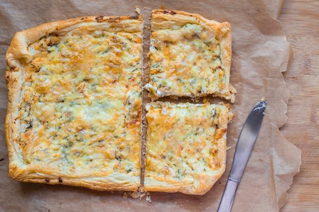 Pysznie prosta tarta serowa z zielonym groszkiem i jajkami na pergaminie. letnia tarta. widok z góry