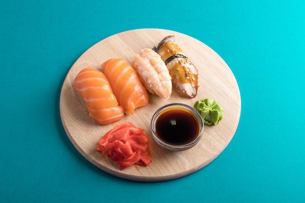 Pyszny apetyczny zestaw sushi nigiri podany na drewnianych talerzach z sosem sojowym i pałeczkami.