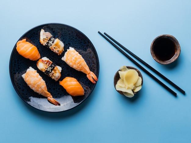 Pyszny apetyczny zestaw sushi podany na glinianym talerzu z sosem sojowym i pałeczkami płasko leżącymi na niebiesko