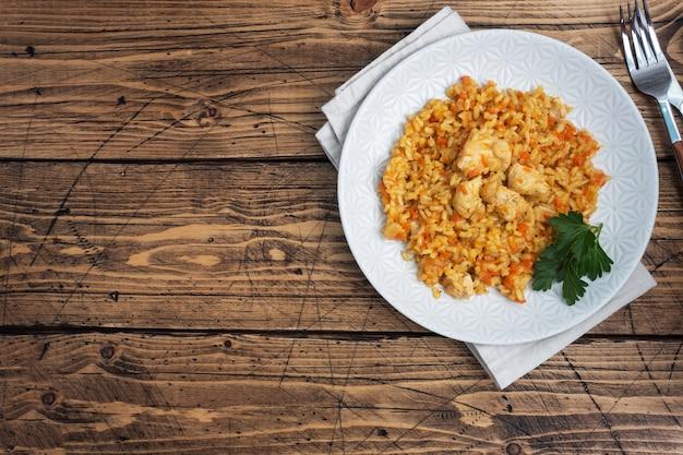 Pyszny azjatycki pilaw, duszony ryż z warzywami i kurczakiem na talerzu. drewniane rustykalne. skopiuj miejsce.