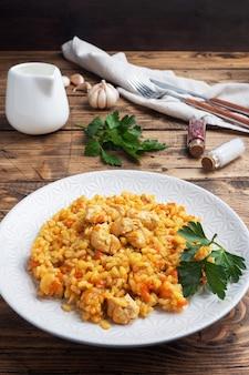 Pyszny azjatycki pilaw, duszony ryż z warzywami i kurczakiem na talerzu. drewniane rustykalne.