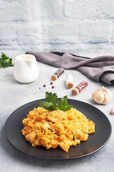 Pyszny azjatycki pilaw, duszony ryż z warzywami i kurczakiem na talerzu. szare tło betonowe.