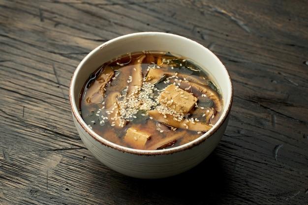 Pyszny azjatycki street food - zupa miso z sezamem, tofu, grzybami shiitake w białej misce na drewnianej powierzchni