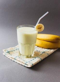Pyszny bananowy koktajl mleczny w szkle na szarym stole
