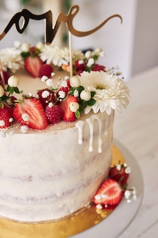 Pyszny biały tort weselny z czerwonymi jagodami, kwiatami i topperem