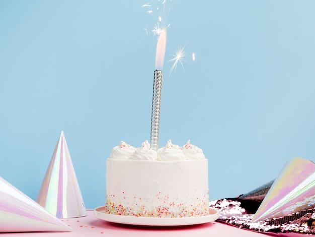 Pyszny biały tort z czapkami urodzinowymi