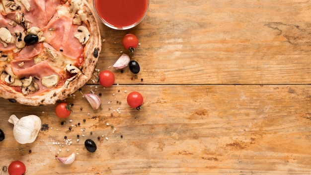 Pyszny boczek; pizza z grzybami w pobliżu czosnku; pomidor wiśniowy; czarna oliwka i miska sosu pomidorowego na drewnianym biurku