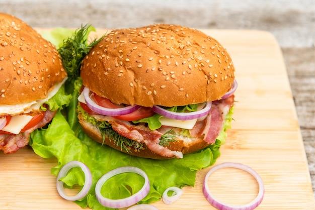 Pyszny burger domowej roboty ze smażonym boczkiem na desce.