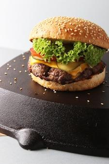 Pyszny burger na czarnej powierzchni na białym tle na białej powierzchni