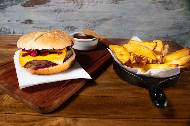 Pyszny burger z serem cheddar i grillowanym wędzonym boczkiem na domowym pieczywie w towarzystwie efektownych rustykalnych ziemniaków i domowego sosu barbecue.