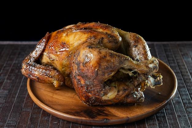 """Pyszny cały grillowany kurczak na drewnianym talerzu. kuchnia peruwiańska """"pollo a la brasa""""."""