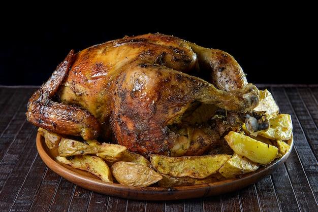 """Pyszny cały grillowany kurczak z kawałkami ziemniaków na drewnianym talerzu. kuchnia peruwiańska """"pollo a la brasa con papas fritas""""."""