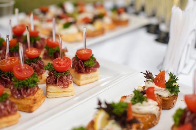 Pyszny canape z kiełbasą i pomidorem. kanapki na białych ceramicznych talerzach na weselu.