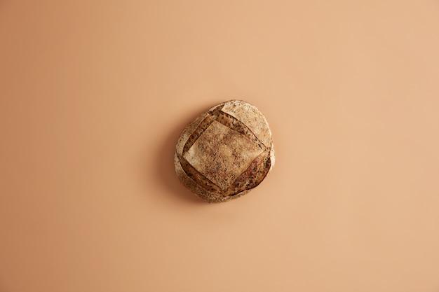 Pyszny chleb wieloziarnisty z różnych ziaren leży na brązowym tle. koncepcja piekarni i smaczne jedzenie. okrągły bochenek chleba gotowy do spożycia. żywienie ekologiczne, naturalne odżywianie, rolnictwo