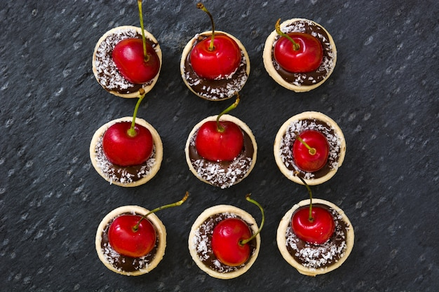 Pyszny czekoladowy tarta z wzorem wiśni i kokosa na czarnej ścianie