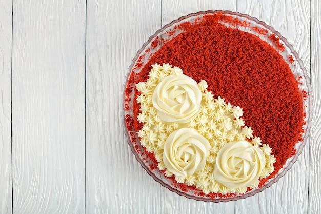 Pyszny czerwony aksamitny tort zwieńczony pięknymi kremowymi różami