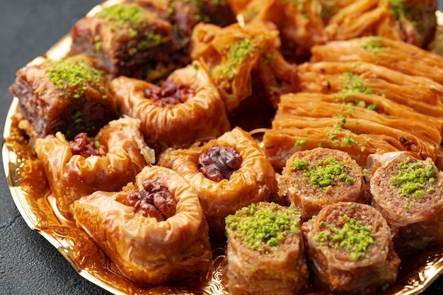 Pyszny deser baklawy w orientalnej oprawie na czarnym tle