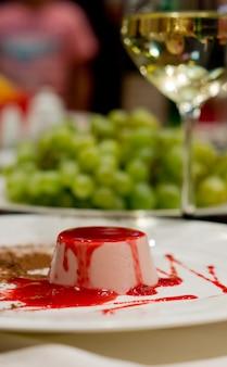 Pyszny deser musowy skropiony bogatą czerwoną owocową polewą podawany na stole z lampką białego wina