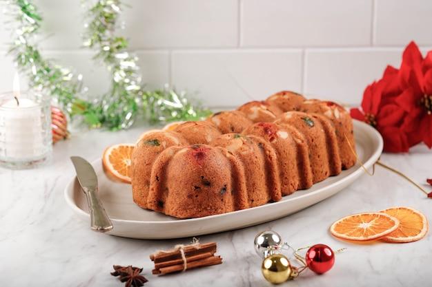 Pyszny domowy budyń z ciasta owocowego angielskiego z suszonymi mieszanymi owocami, sułtankami, rodzynkami i siekanymi migdałami. serwowane podczas świąt bożego narodzenia lub sylwestra
