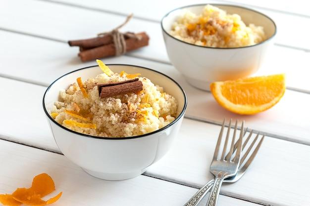 Pyszny domowy kuskus z pomarańczami i cynamonem na rustykalnym drewnianym tle. smaczne wegańskie jedzenie.
