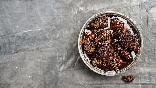 Pyszny dżem z szyszek sosny dla dzieci w małej misce. tradycyjny syberyjski deser z młodymi szyszkami w kształcie dżemu na szarej fakturze