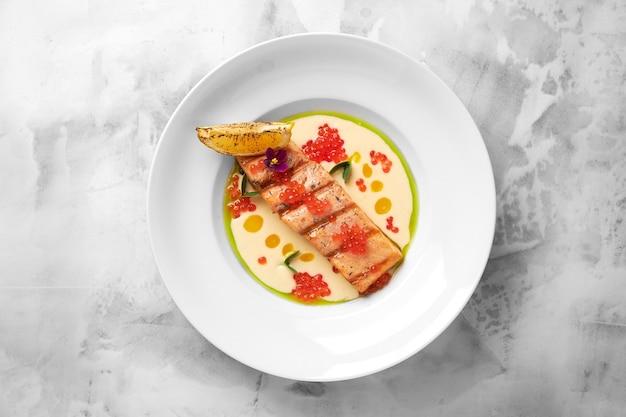 Pyszny Filet Z łososia Z Grilla Z Kremowym Sosem W Białym Talerzu Na Jasnym Tle. Smaczne Owoce Morza Premium Zdjęcia