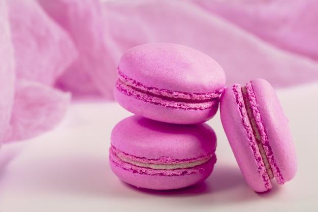 Pyszny francuski deser. trzy delikatne pastelowe różowe fioletowe ciasta macaron lub makaronik na zwiewnej tkaninie,