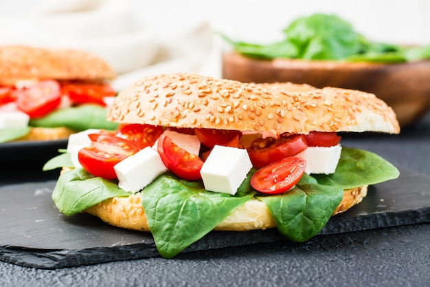 Pyszny gotowy do spożycia bajgiel nadziewany pomidorami, fetą i liśćmi szpinaku na czarnym tle. lekka zdrowa przekąska. zbliżenie