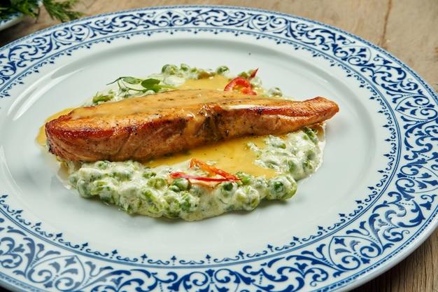 Pyszny grillowany filet z łososia z groszkiem w kremowym sosie na białym talerzu na drewnianej powierzchni. smaczne owoce morza