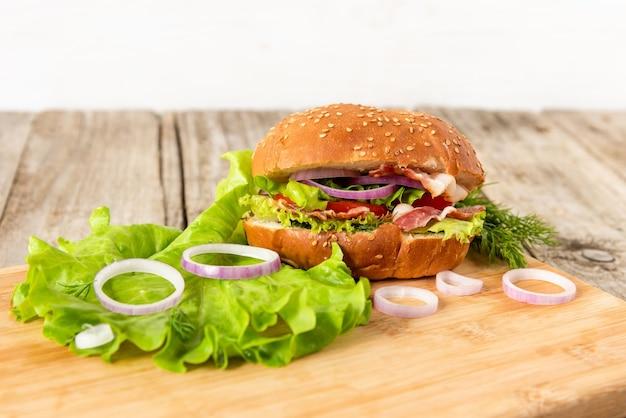 Pyszny hamburger z boczkiem i ziołami na desce.