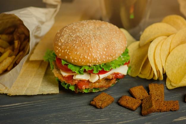 Pyszny hamburger z frytkami, przekąskami i frytkami. mix przekąsek. pyszny burger i słona przekąska, w tym chipsy ziemniaczane