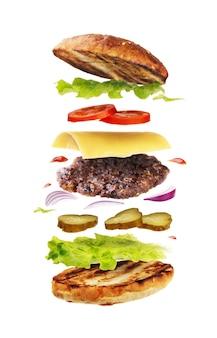 Pyszny hamburger z latającymi składnikami na białej powierzchni